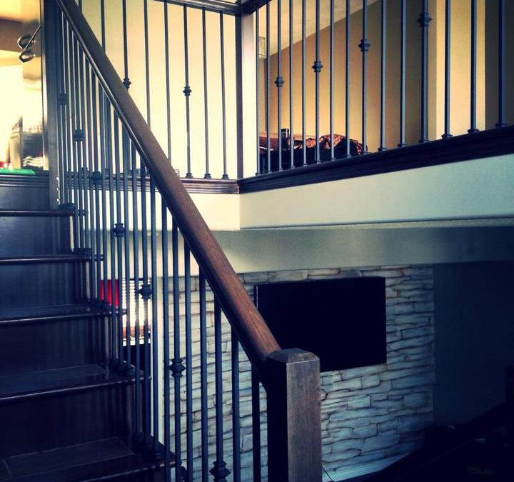 Stained maple railing renovation with black metal spindles