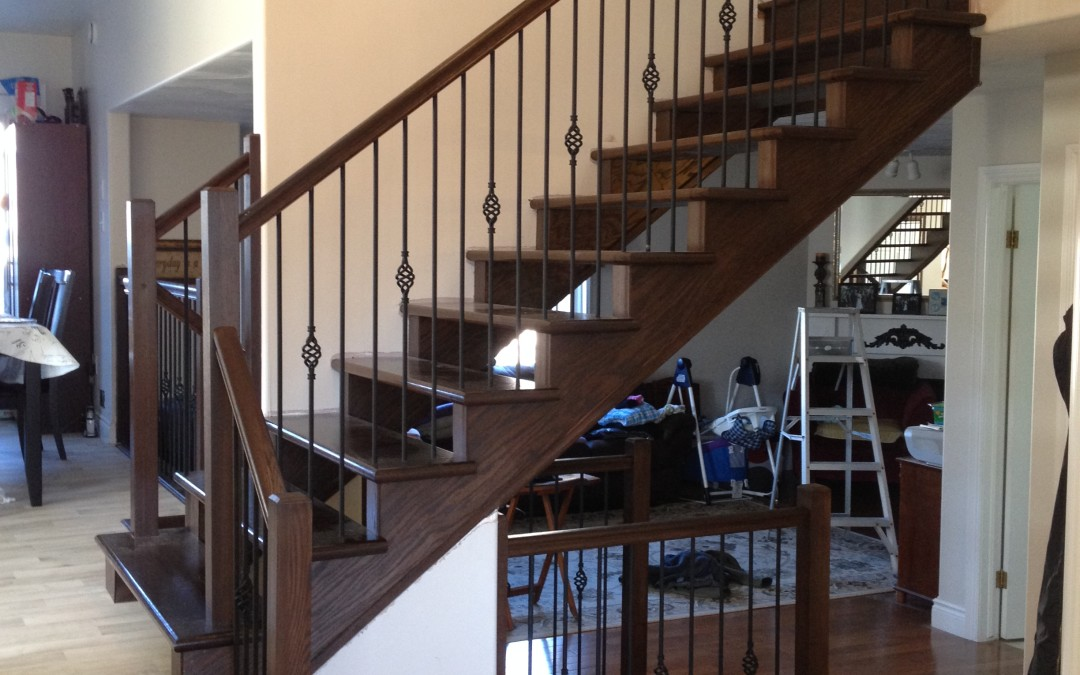 Custom open riser staircase with birdcage wrought iron spindles